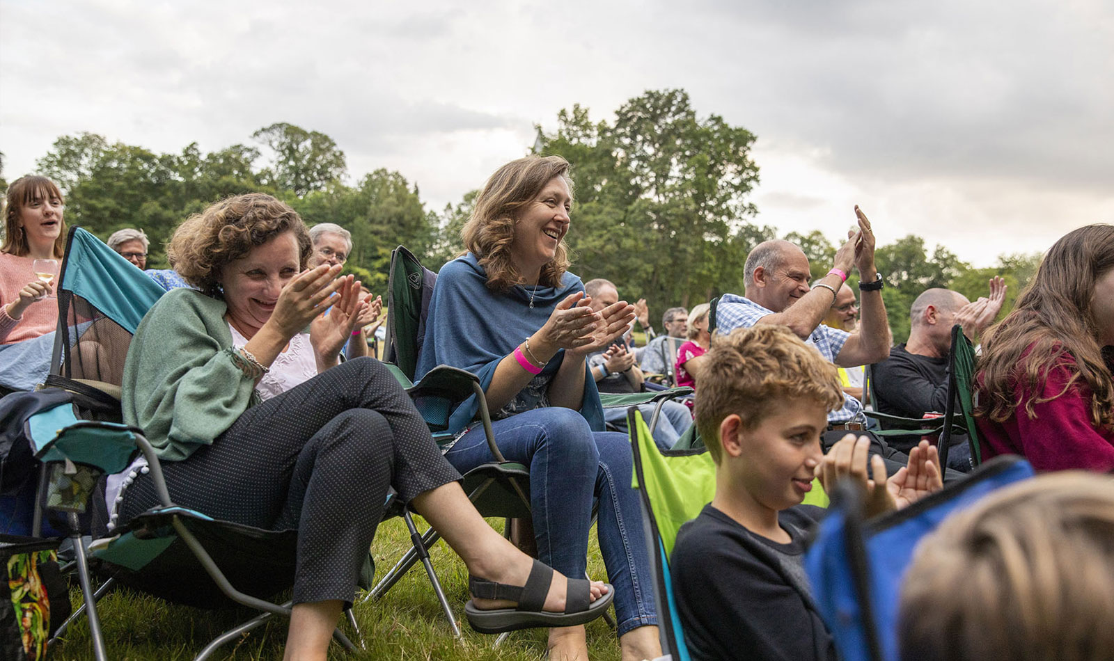 Families sitting outdoors clapping